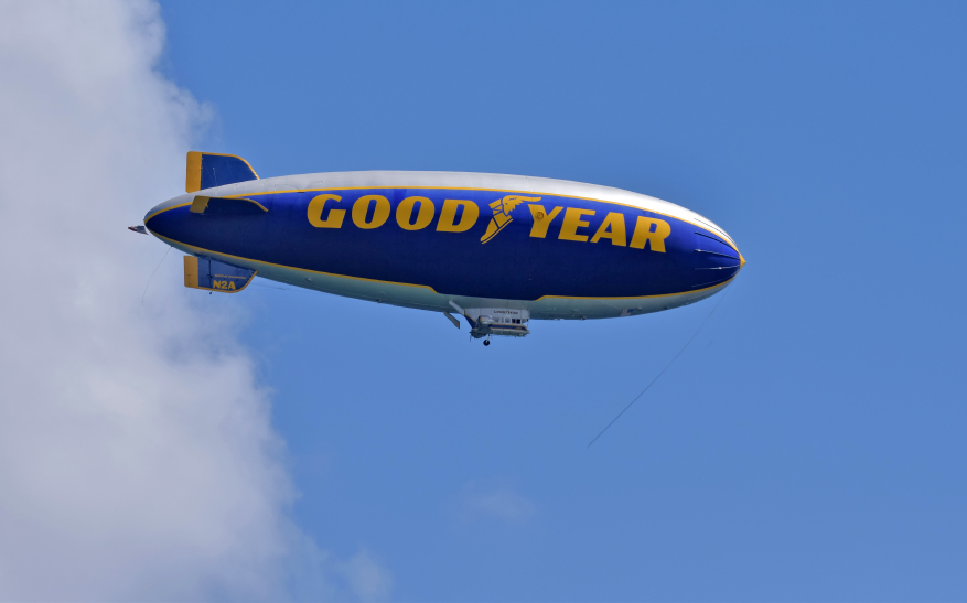 A promotional Goodyear Blimp soaring through the clouds.