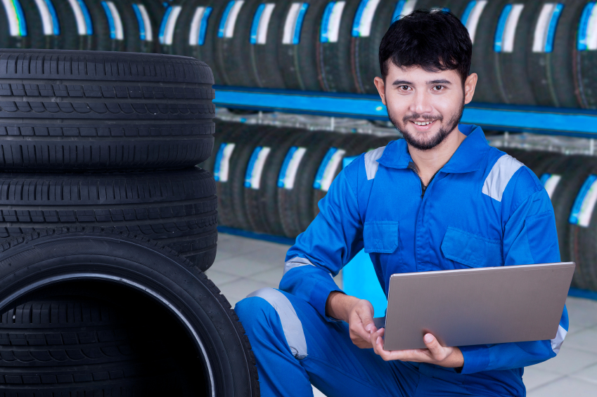 Mechanic using laptop to check tires