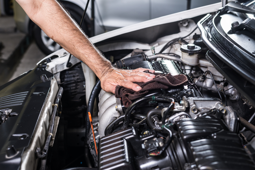 An automotive training pro works on an engine