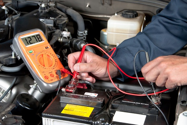 Mechanics use a multimeter during electrical repairs