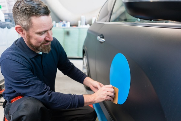 You may get practice installing company logos on cars
